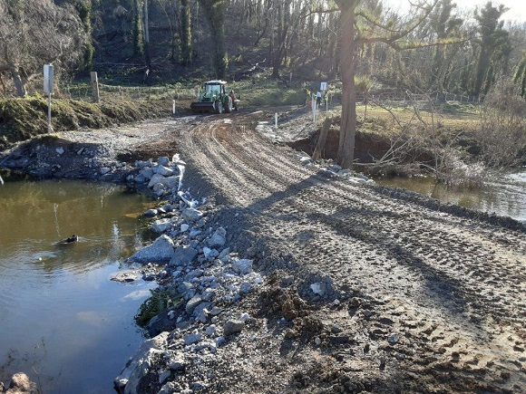 A tractor restores the material forming a creek crossing