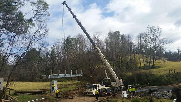 A crane lifts a section of bridge