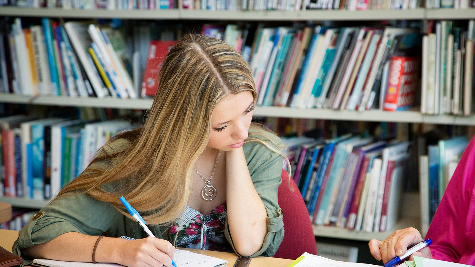 A young woman taking notes from a library book into her own notebook banner image
