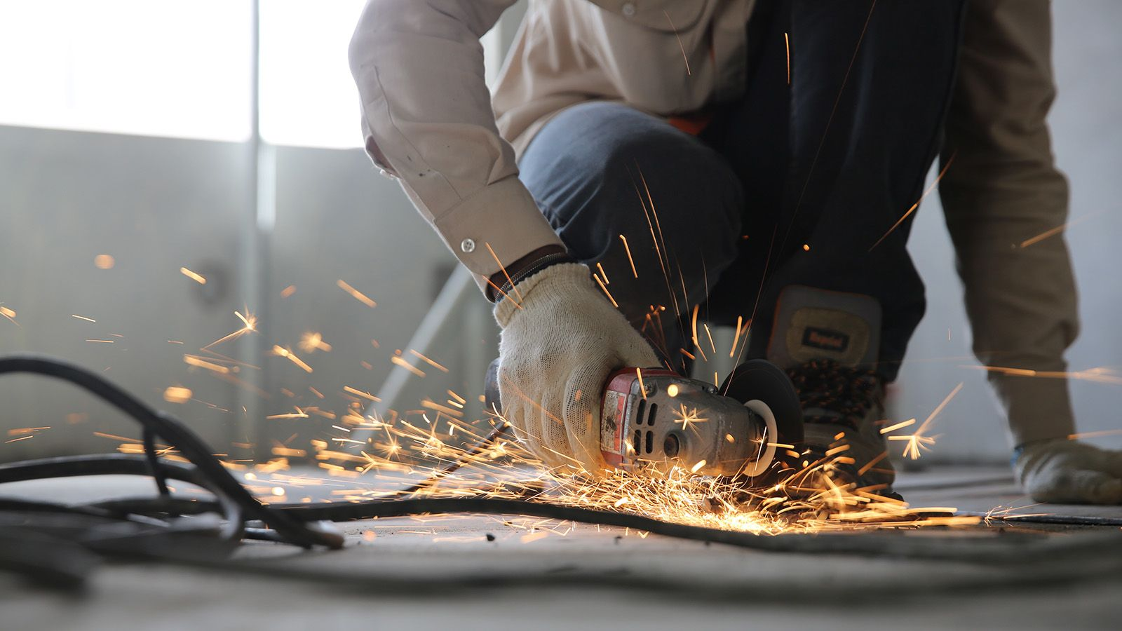 A man using a grinder powertool, creating sparks banner image