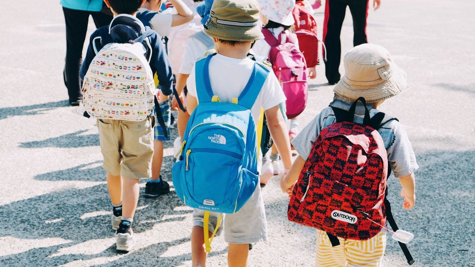 A student in a yellow school uniform shirt writing in a notebook at a desk banner image