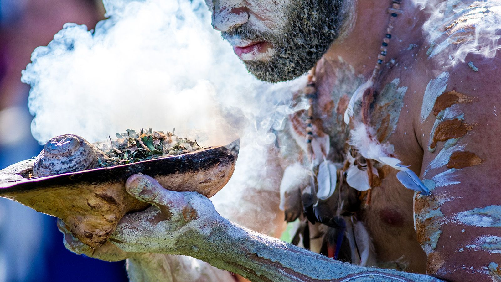 Close cropped photo of a man performing a traditional smoking ceremony banner image