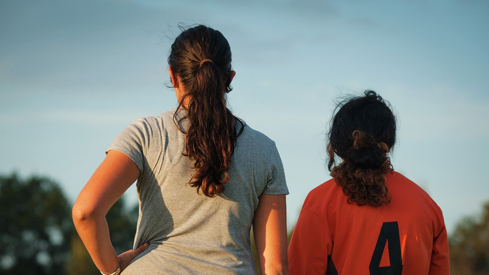 The backs of two women wearing different sporting uniforms banner image
