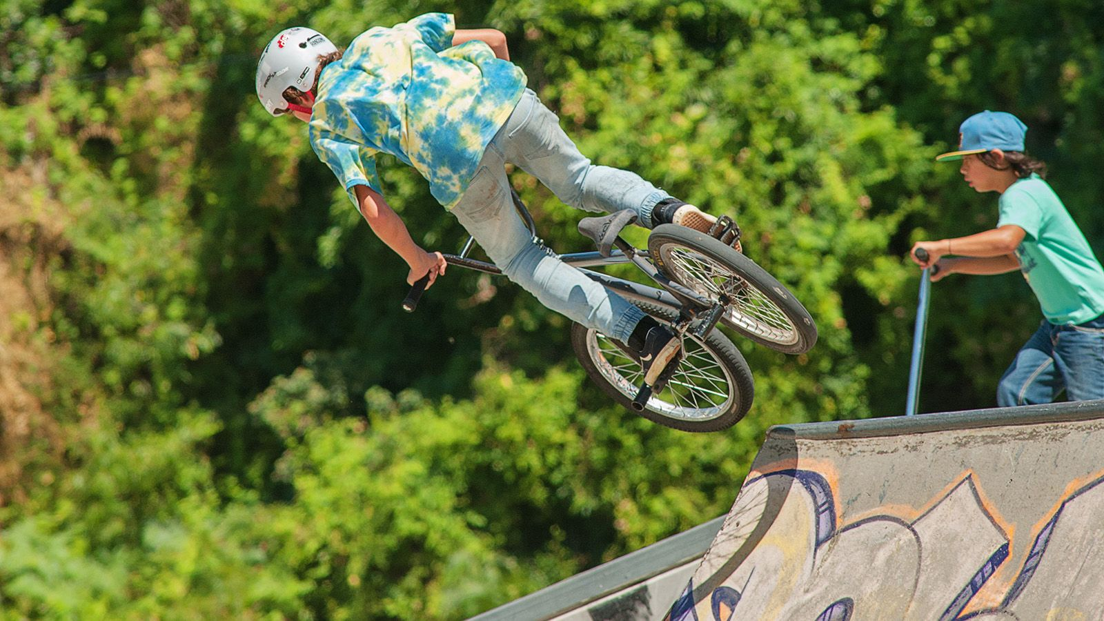 A young man riding a BMX bike in mid-air at a skate park banner image