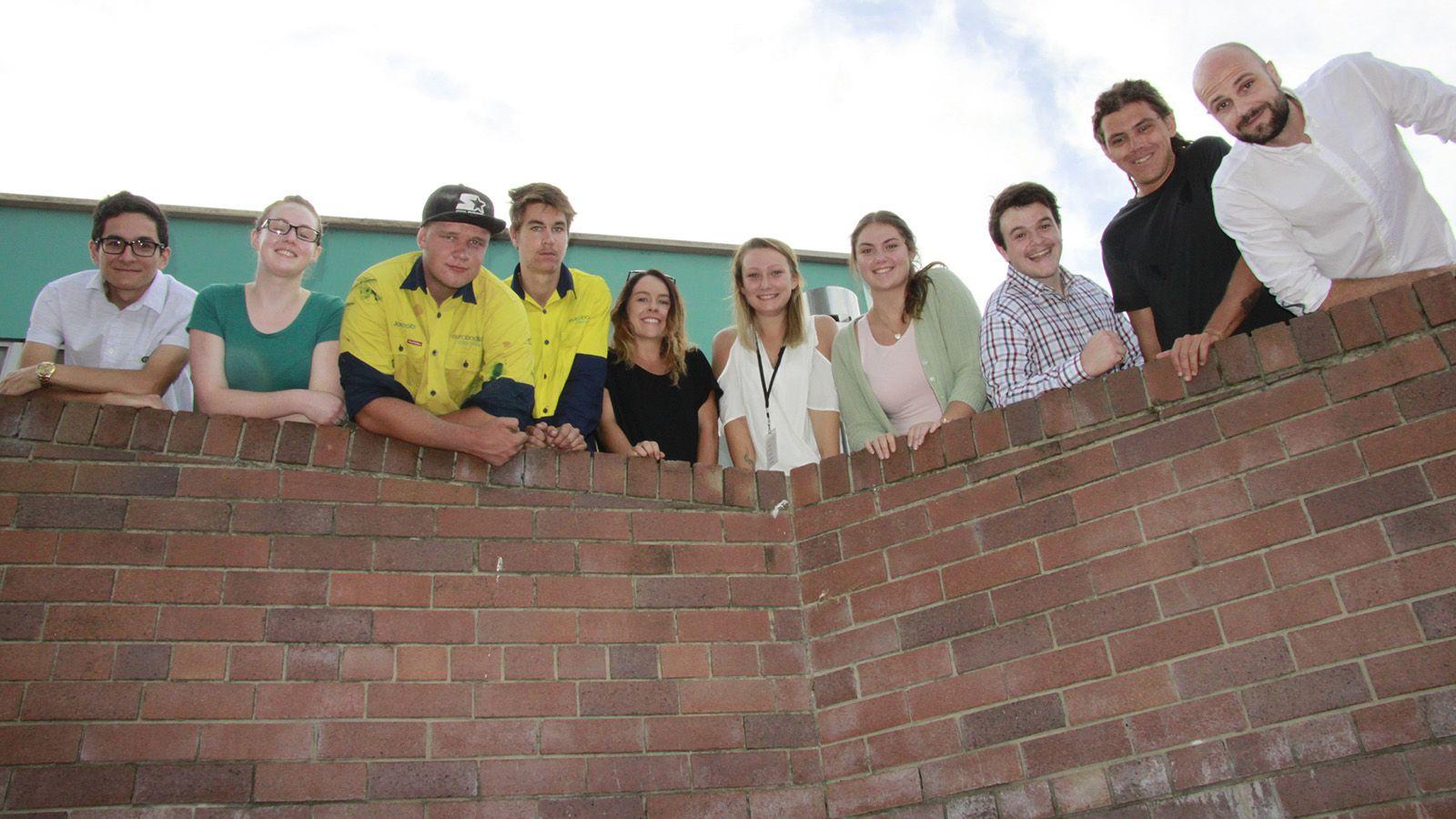 Ten Eurobodalla Council trainees looking over a brick wall banner image