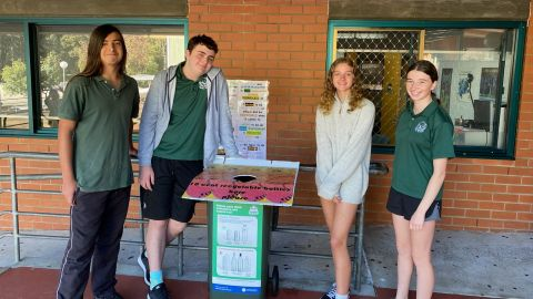 Four students in school uniform stand by a decorated bin.
