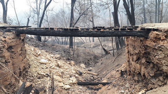 The bridge abutment walls no longer exist and the burnt girders straddle a dry creek bed
