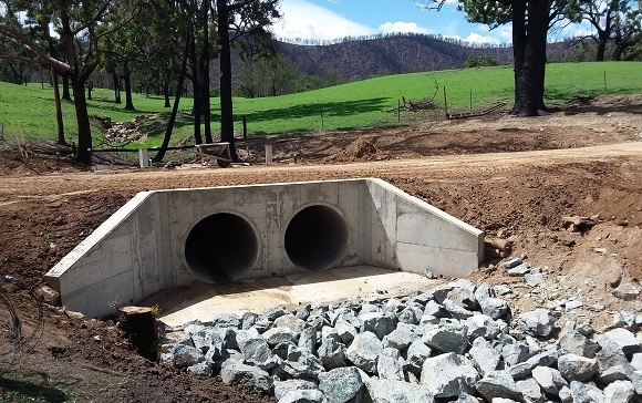 A dirt road passes over concrete pipes where the timber bridge once sat