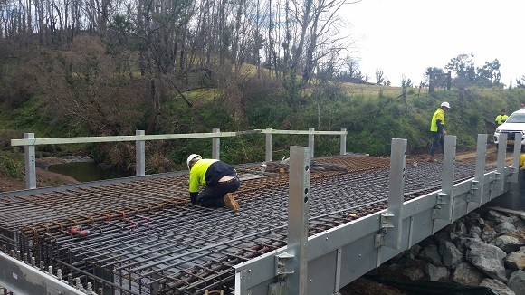 Men tie reinforcing steel in the aluminium bridge
