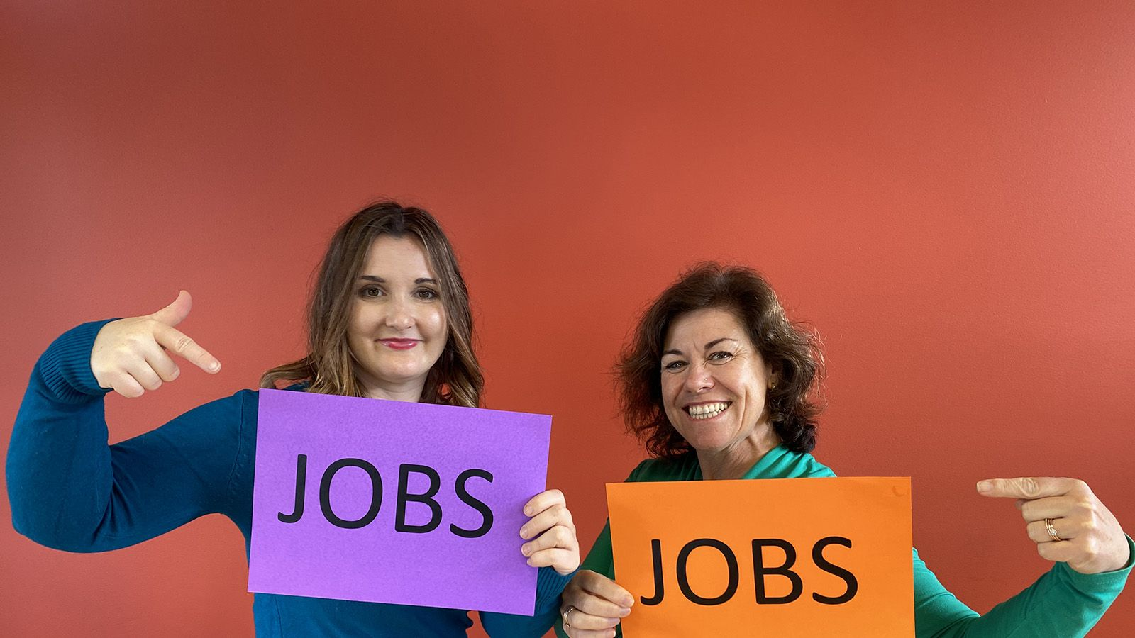 Two Job Shop staff members each holding and pointing to a piece of paper that reads 'JOBS' banner image