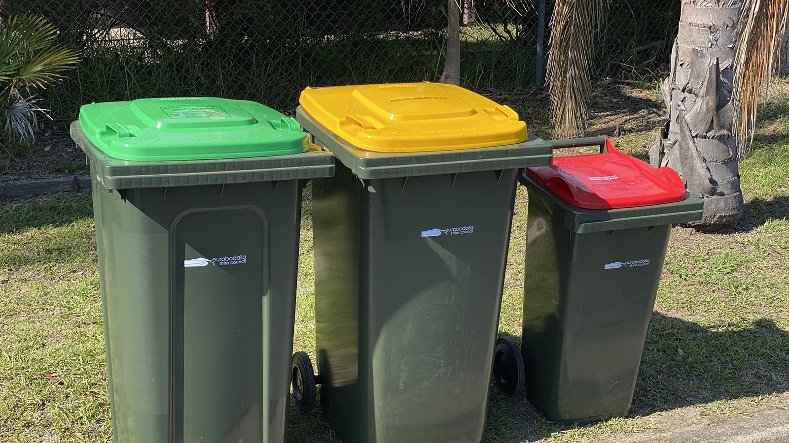 Three household bins, with a gree, yellow, and red lid. banner image