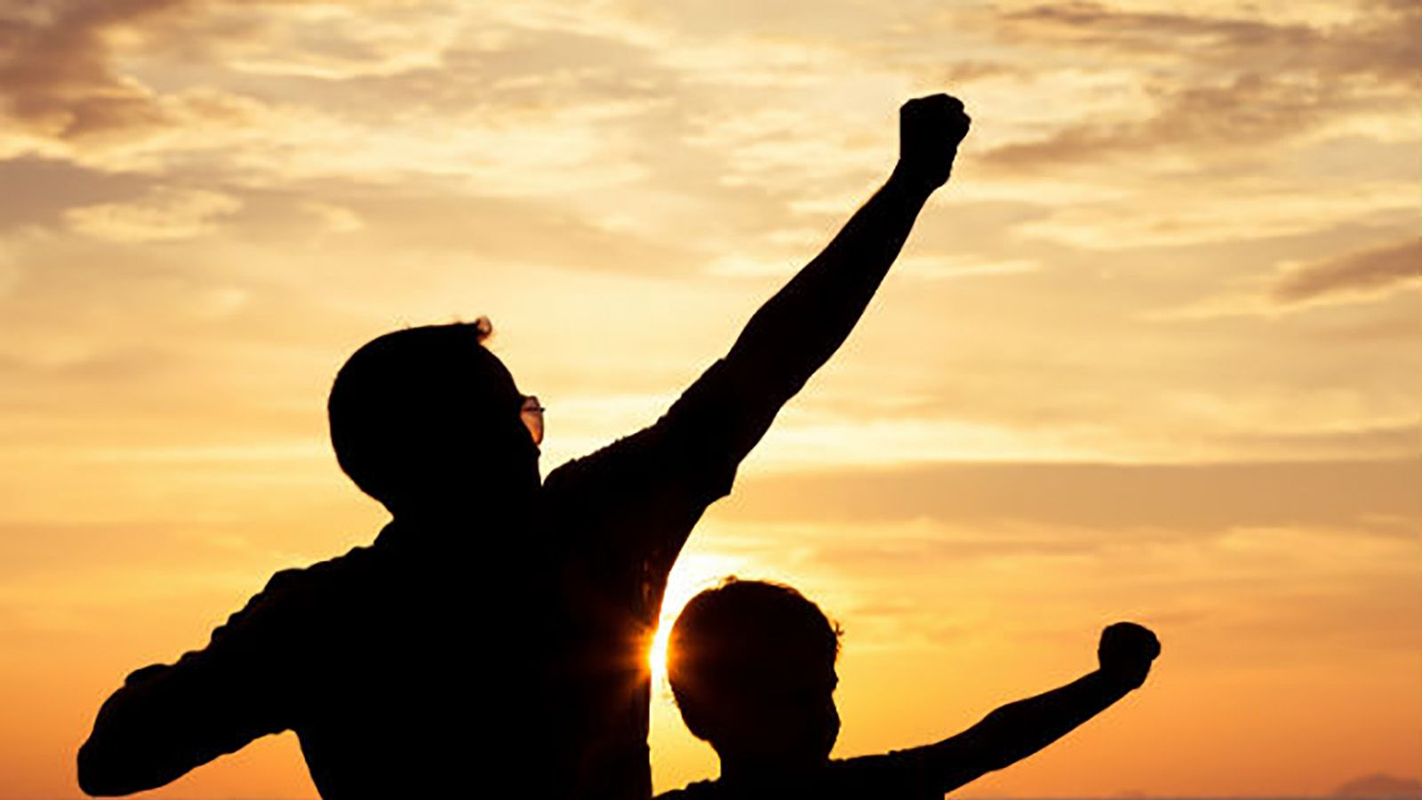 Silhouettes of a man and child with one arm raised into the air banner image