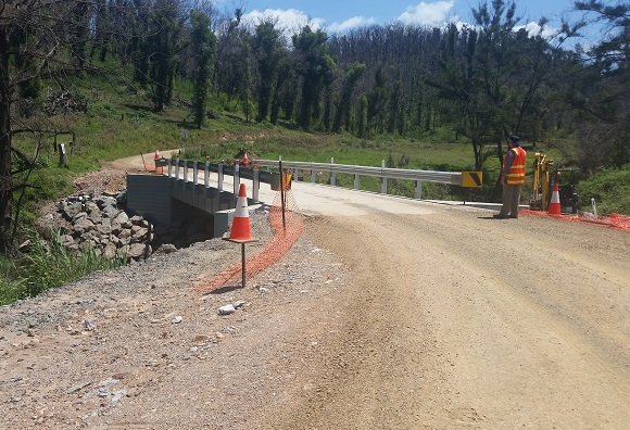 A new bridge with guardrail is positioned on a winding dirt road