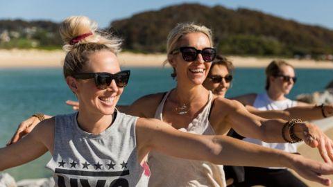 Four women in yoga poses along estuary rockwall