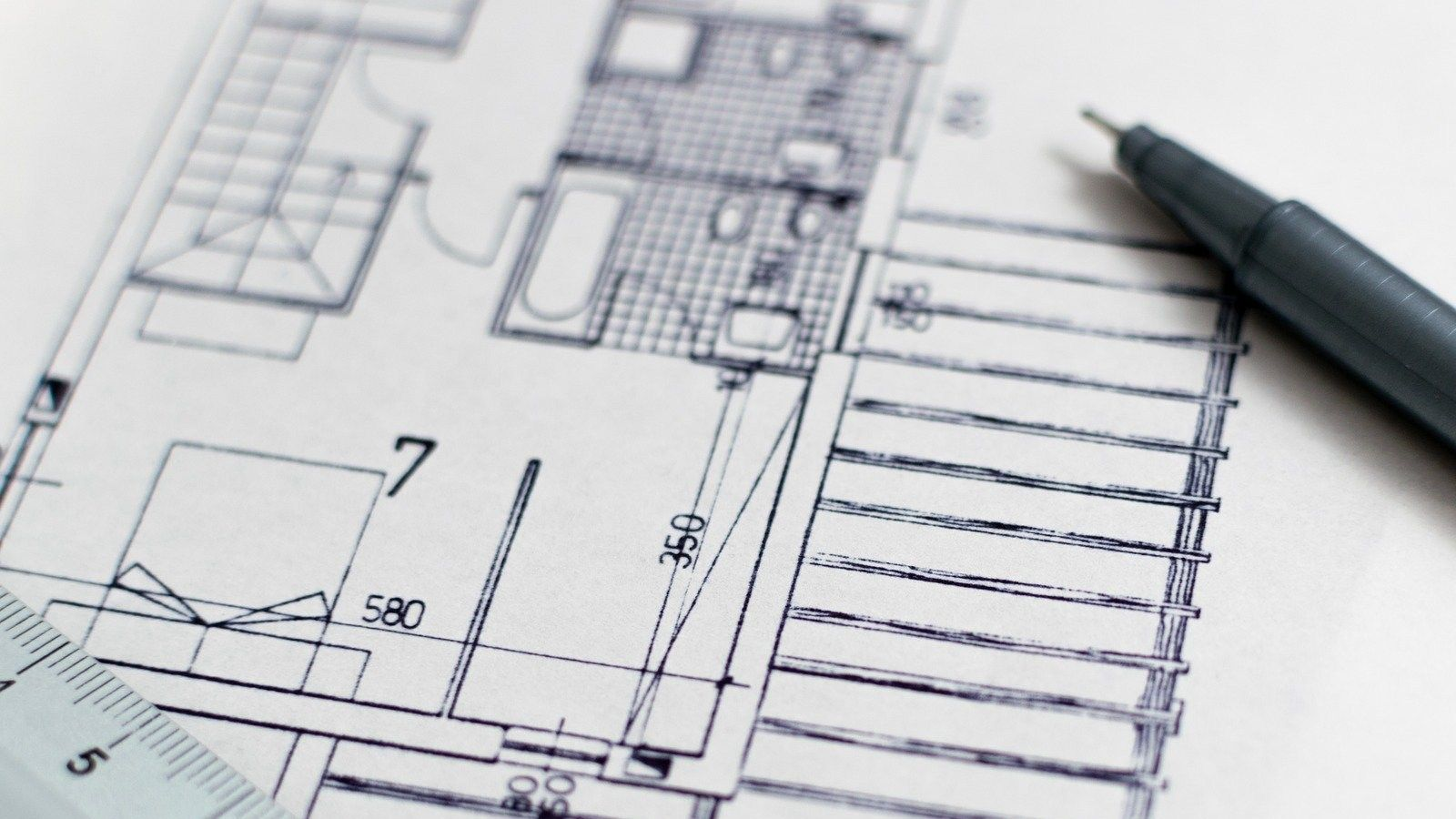 Building plans with black pen laying across them banner image