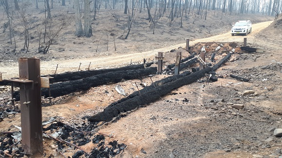 The low timber bridge is burnt to the ground leaving large timbers sitting in the dry creek bed surrounded by burnt forest