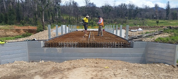 Two men inspect the steel reo mesh supported by aluminum abutments