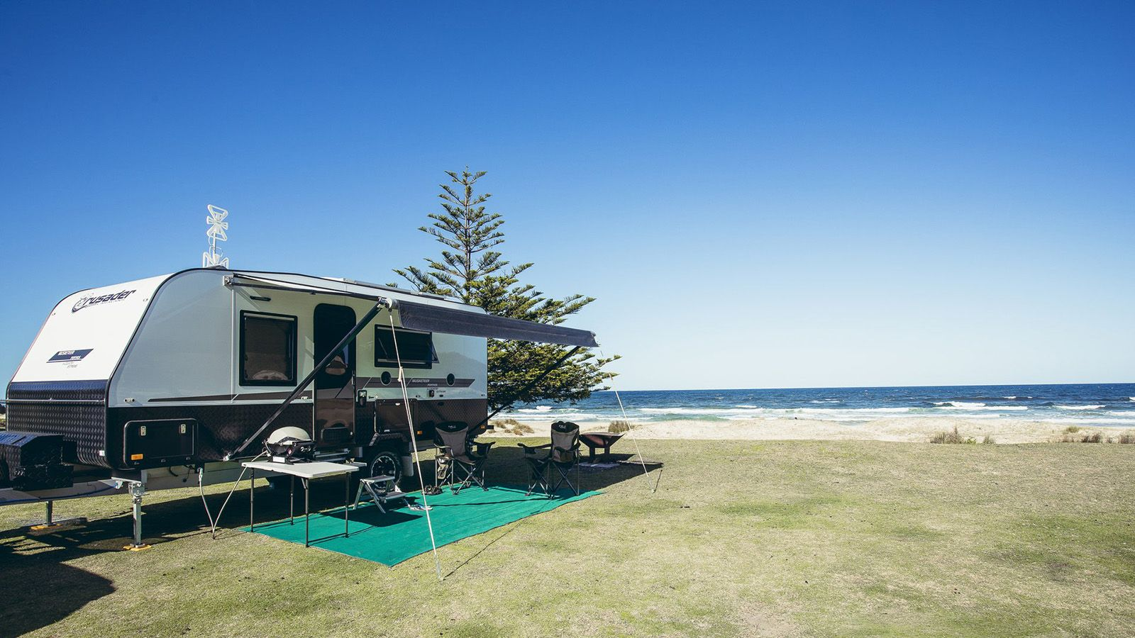 A caravan at a beachside camping ground banner image