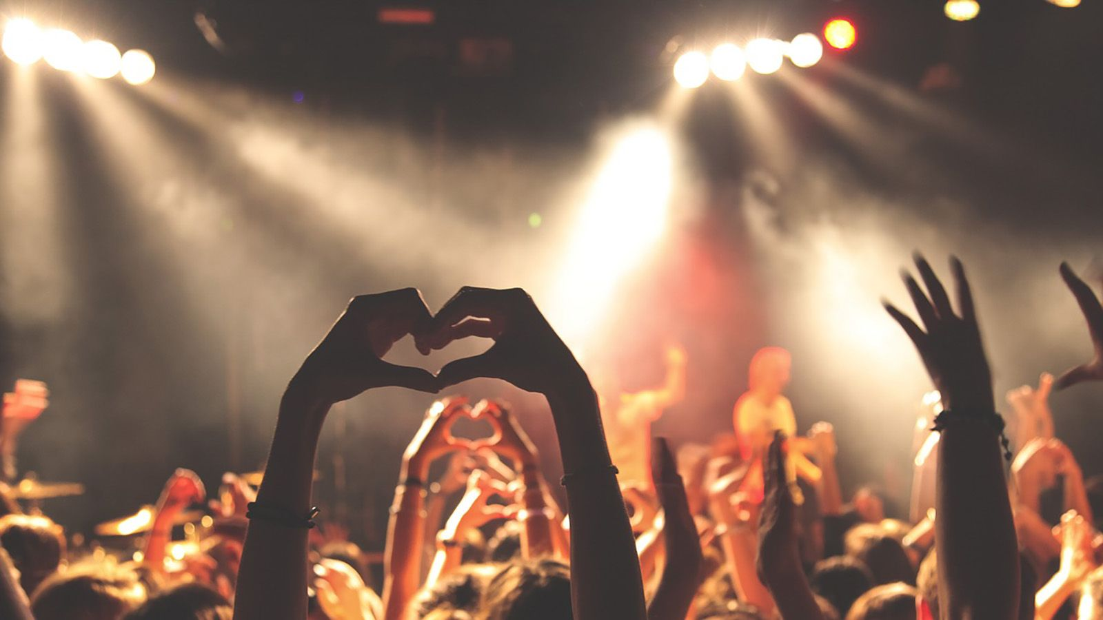 Overhead photograph of a music performance with one crowd member forming their hands into the shape of a heart banner image