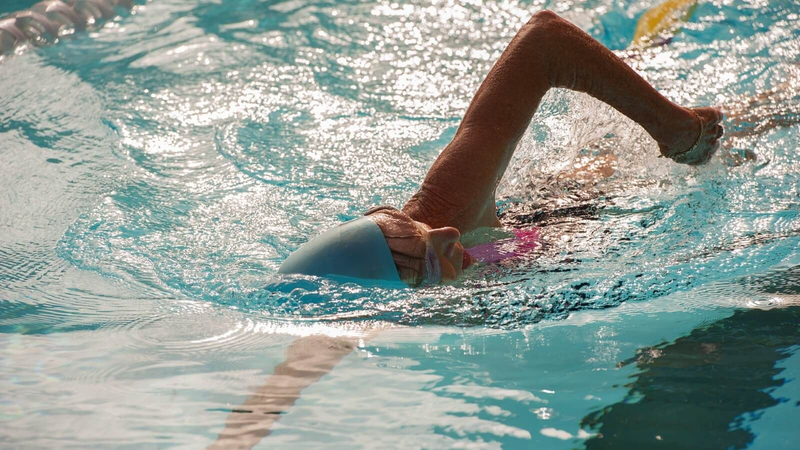 Woman in cap and goggles swimming laps  banner image
