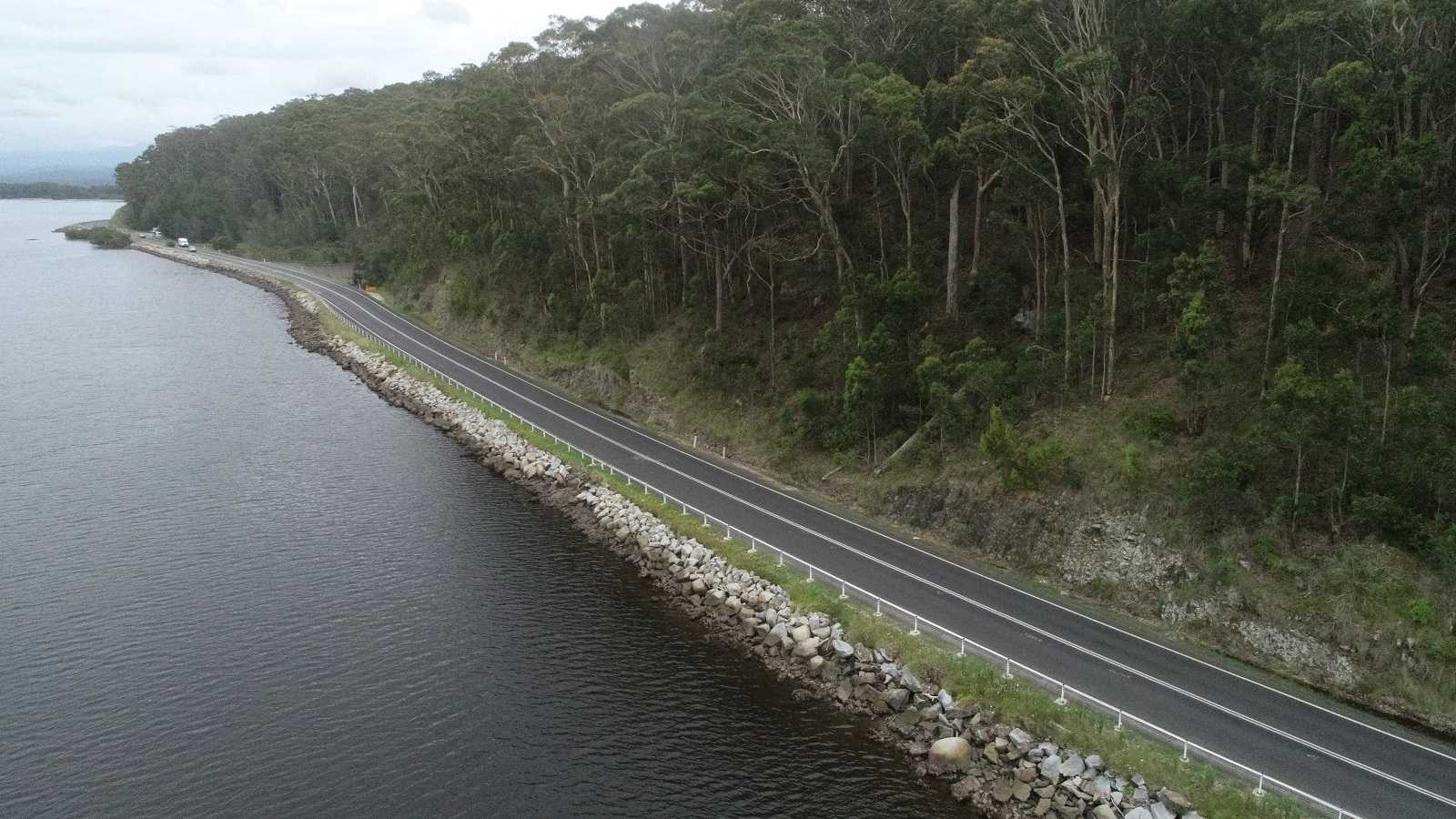 A narrow sealed road follows the edge of a body of water with a forested hill on the otherside