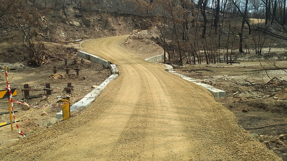 Concrete barriers contain a temporary road built across the dry creek bed
