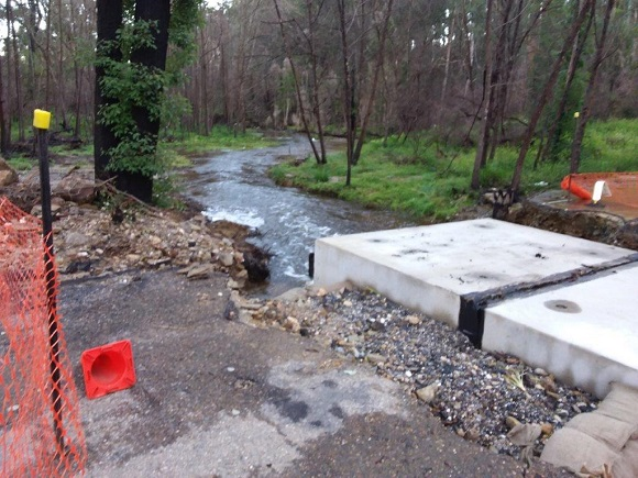 Flood waters flow through newly placed concrete box culverts