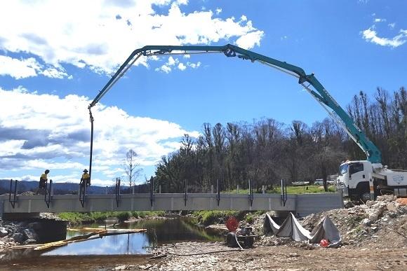 A concrete boom pumps concrete into place to form the new bridge deck