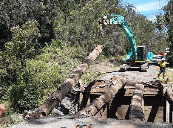 An excavator lifts a large timber bearer from the bridge