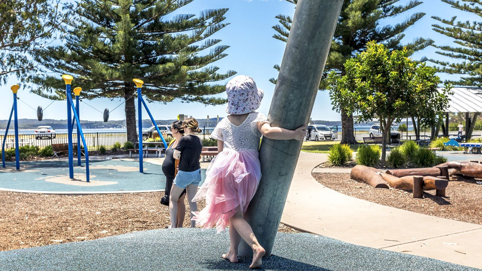 A young girl wearing a pink dress and hat holding onto a pole at Batehaven inclusive playground banner image