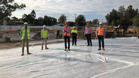 Six men in high-vis vests and hard hats stand on a concrete slab.