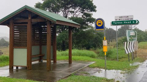 A bus stop next to a road sign pointing to Tuross Head