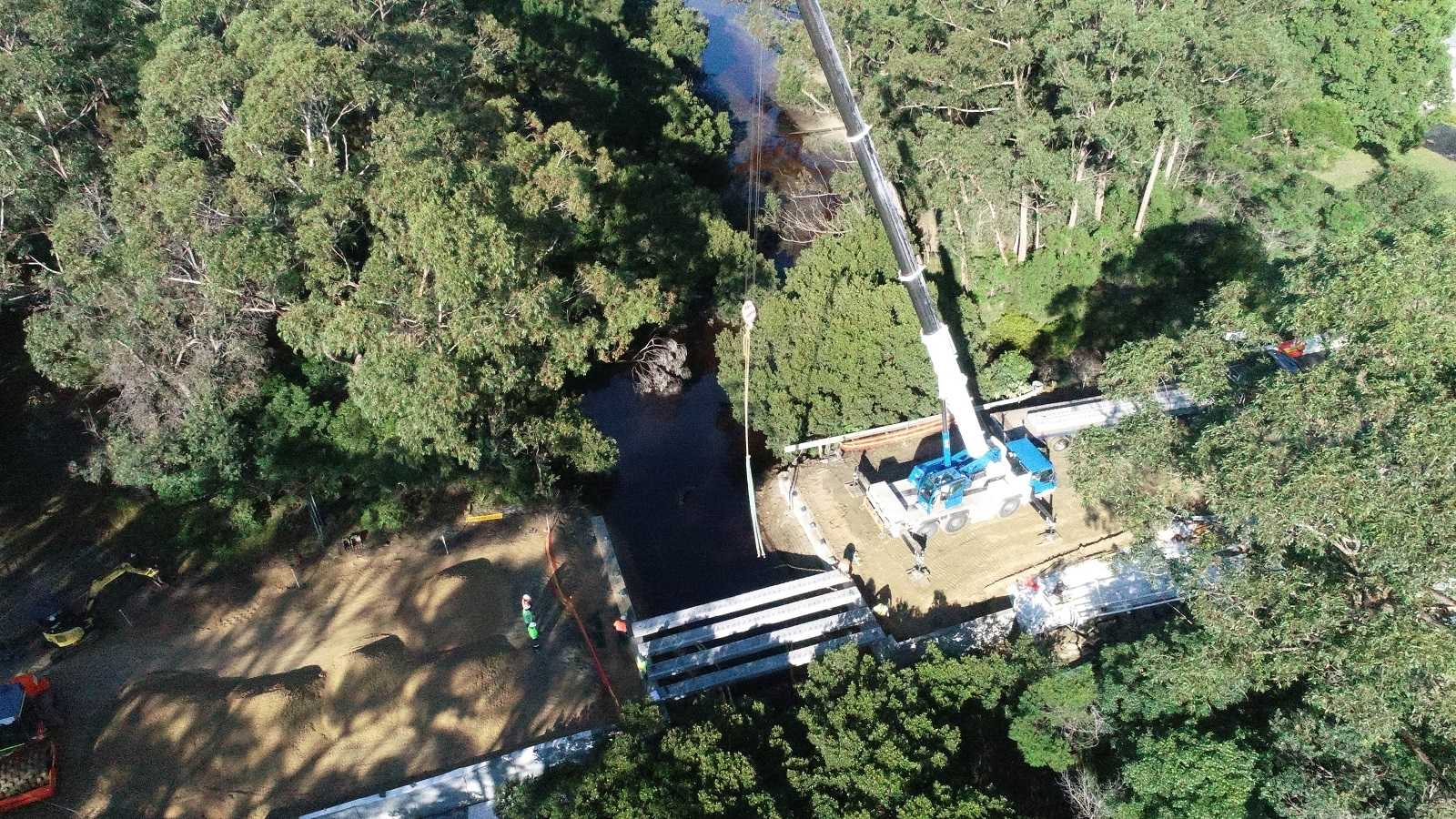 A crane truck lowers huge beams across a creek joining two sections of road.