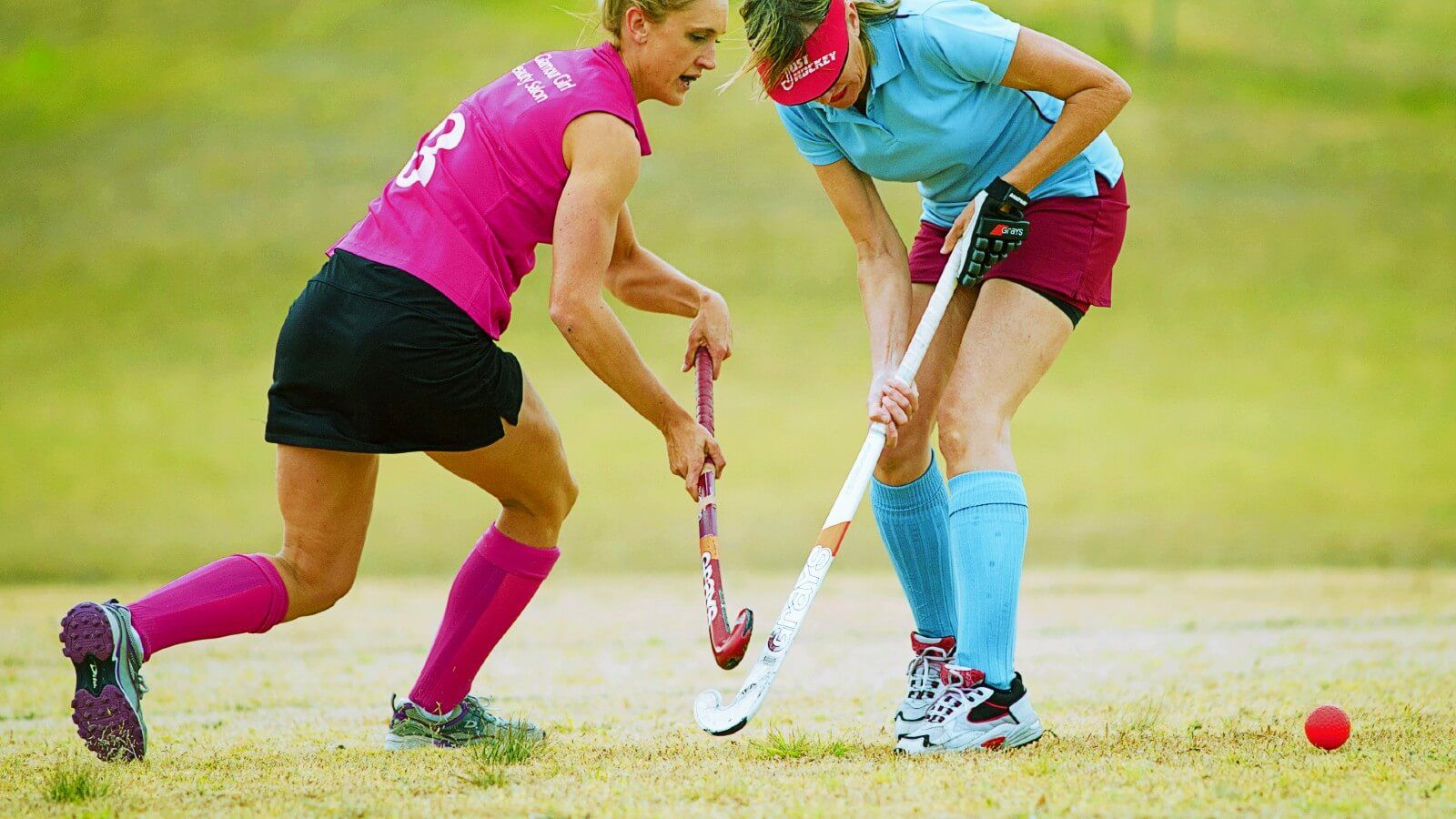 Two women playing hockey banner image