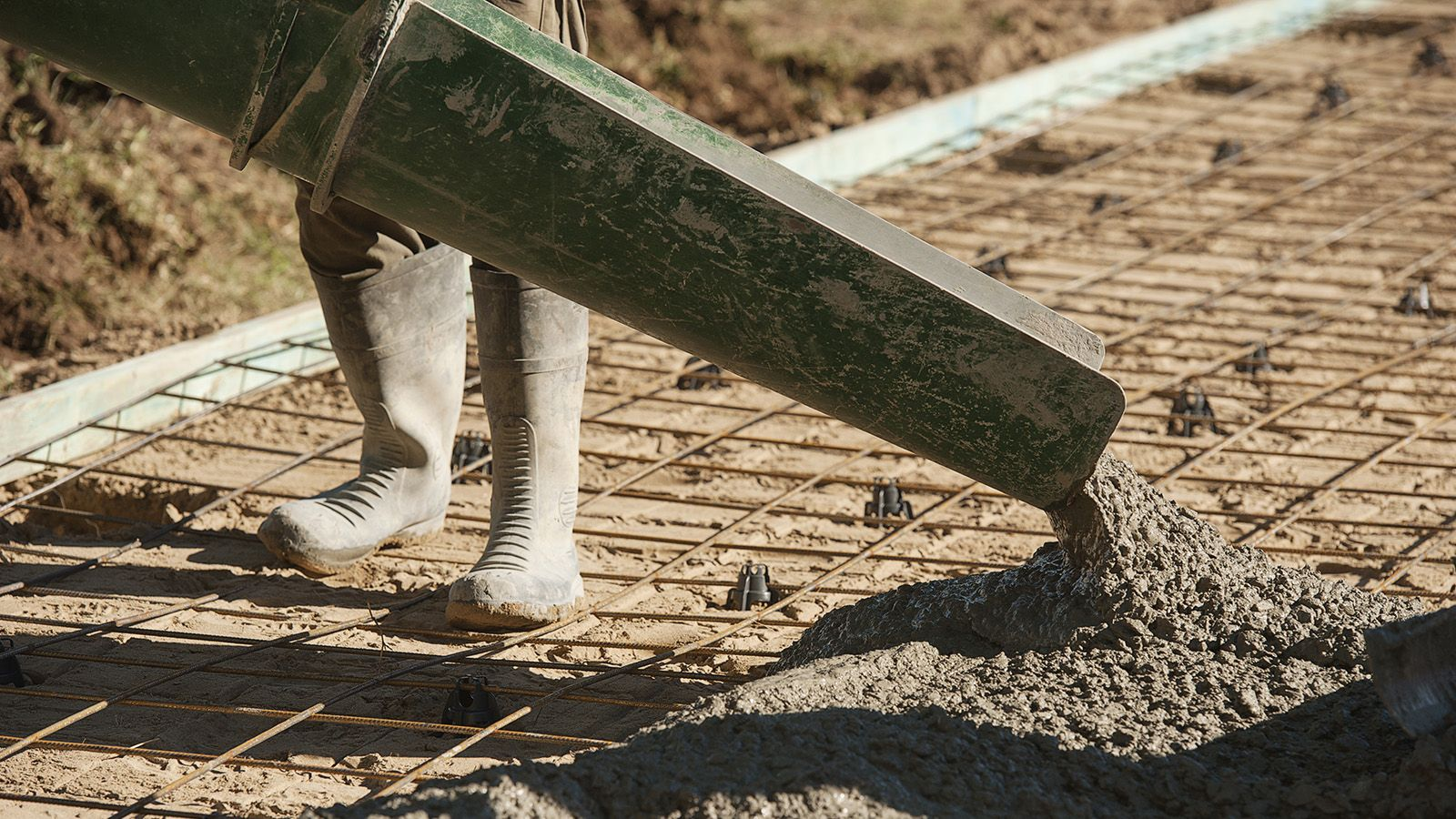 A person wearing gumboots using machinery to pour cement into an area prepared for cement banner image
