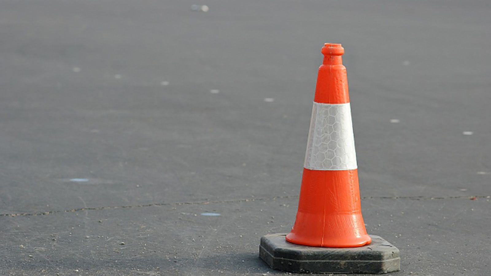 A traffic cone on a bitumen road surface banner image