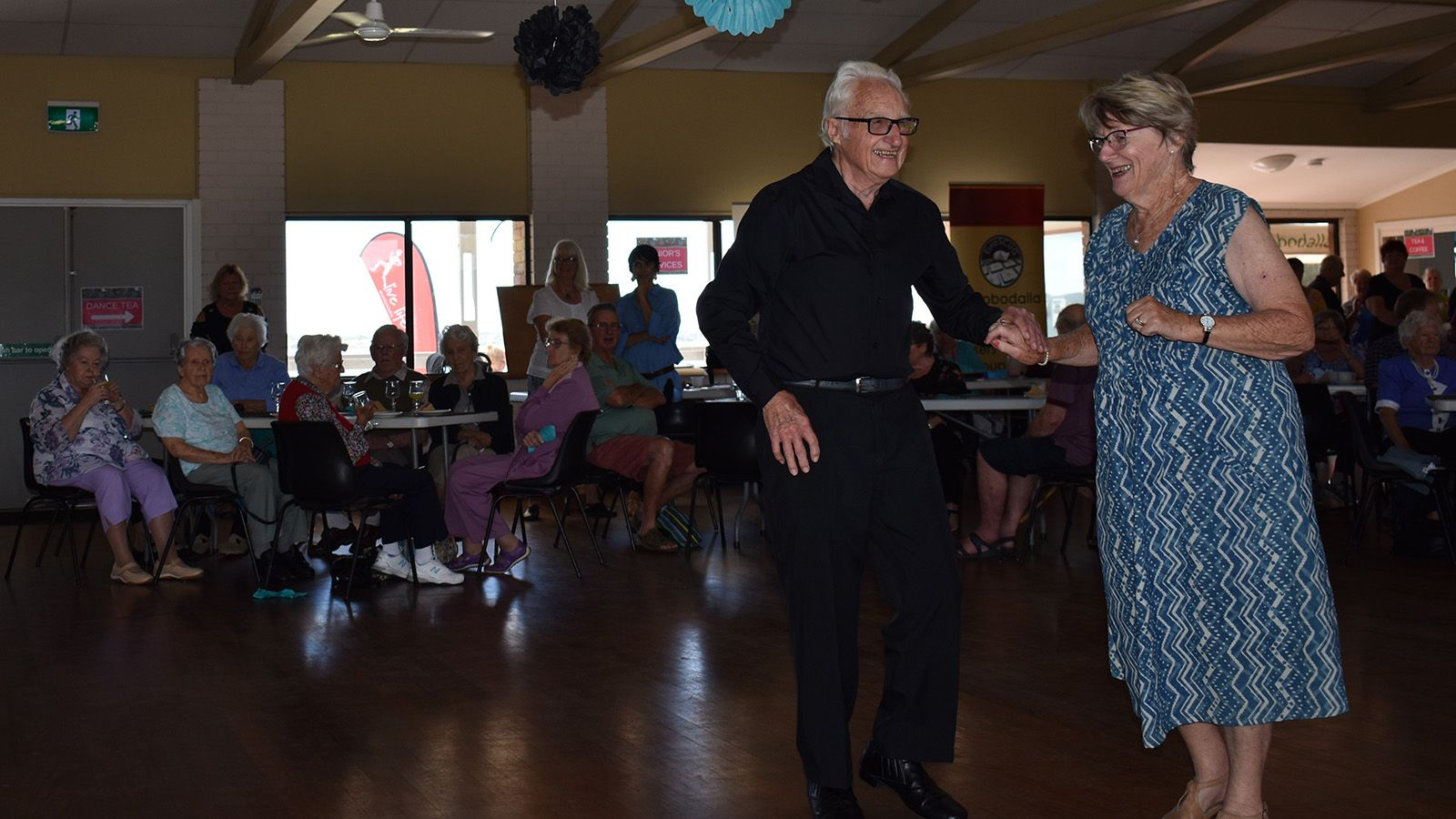 An older man and woman dancing at a social event banner image