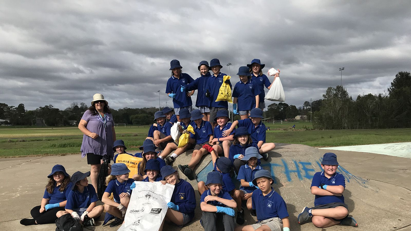 Eurobodalla school students sitting on a ramp at a skate park while holding clean up australia day bags and wearing gloves banner image