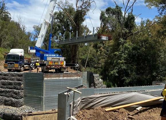 A crane lowers a section of new bridge deck into place