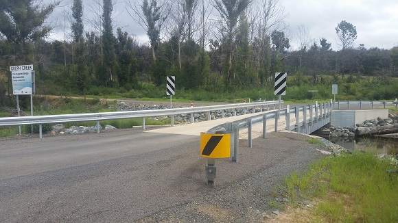 Road signs and guard rail guide motorists across a concrete bridge.