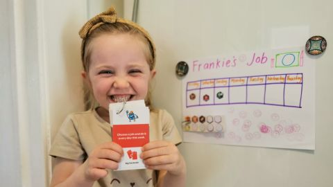 A smilimg child holds up cards next to a jobs chart.
