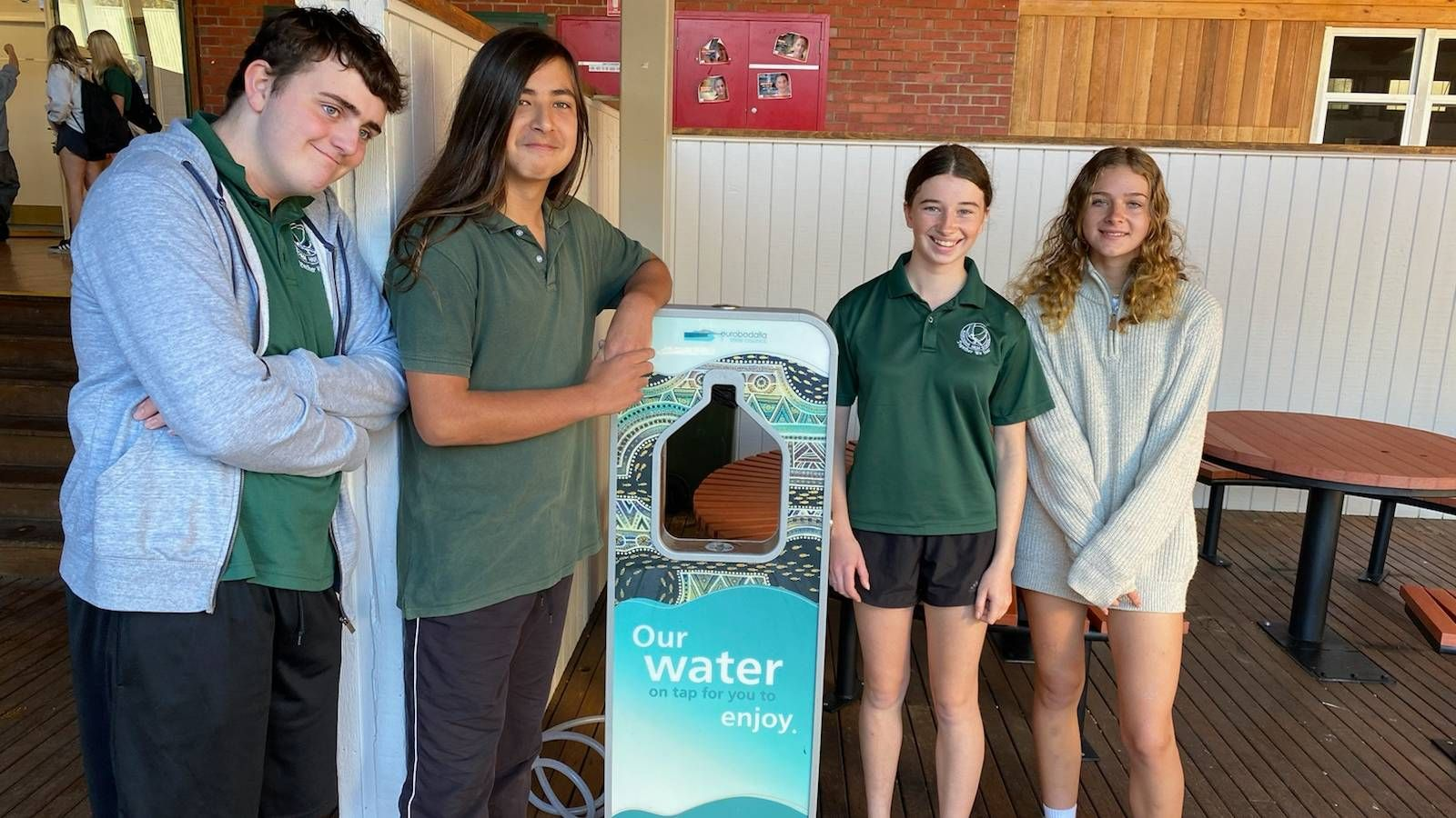 Four high school students standing next to a Council water dispenser banner image