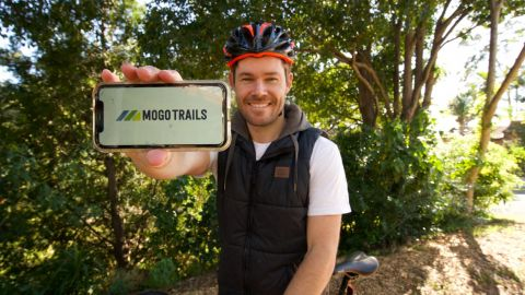 A man on a bike, wearing a bike helmet, holds up a smartphone on which is a logo with the words Mogo Trails.