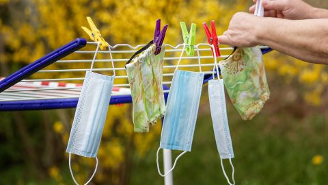 Five face masks on a washing line with yellow flowers in background