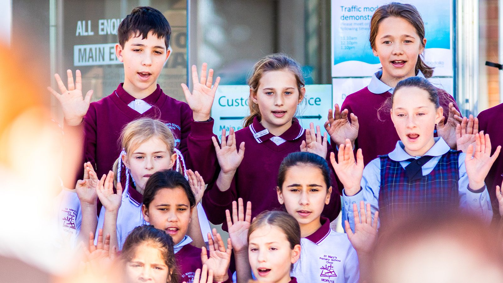 Eight students in Saint Mary's school uniforms perfoming a song banner image