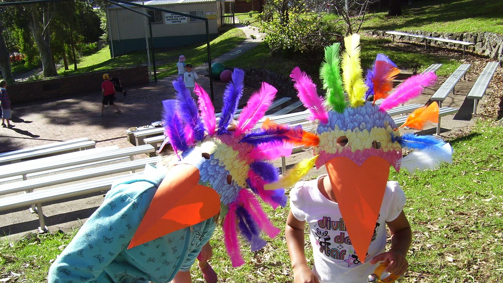 Two children wearing colourful home made bird masks over their faces banner image