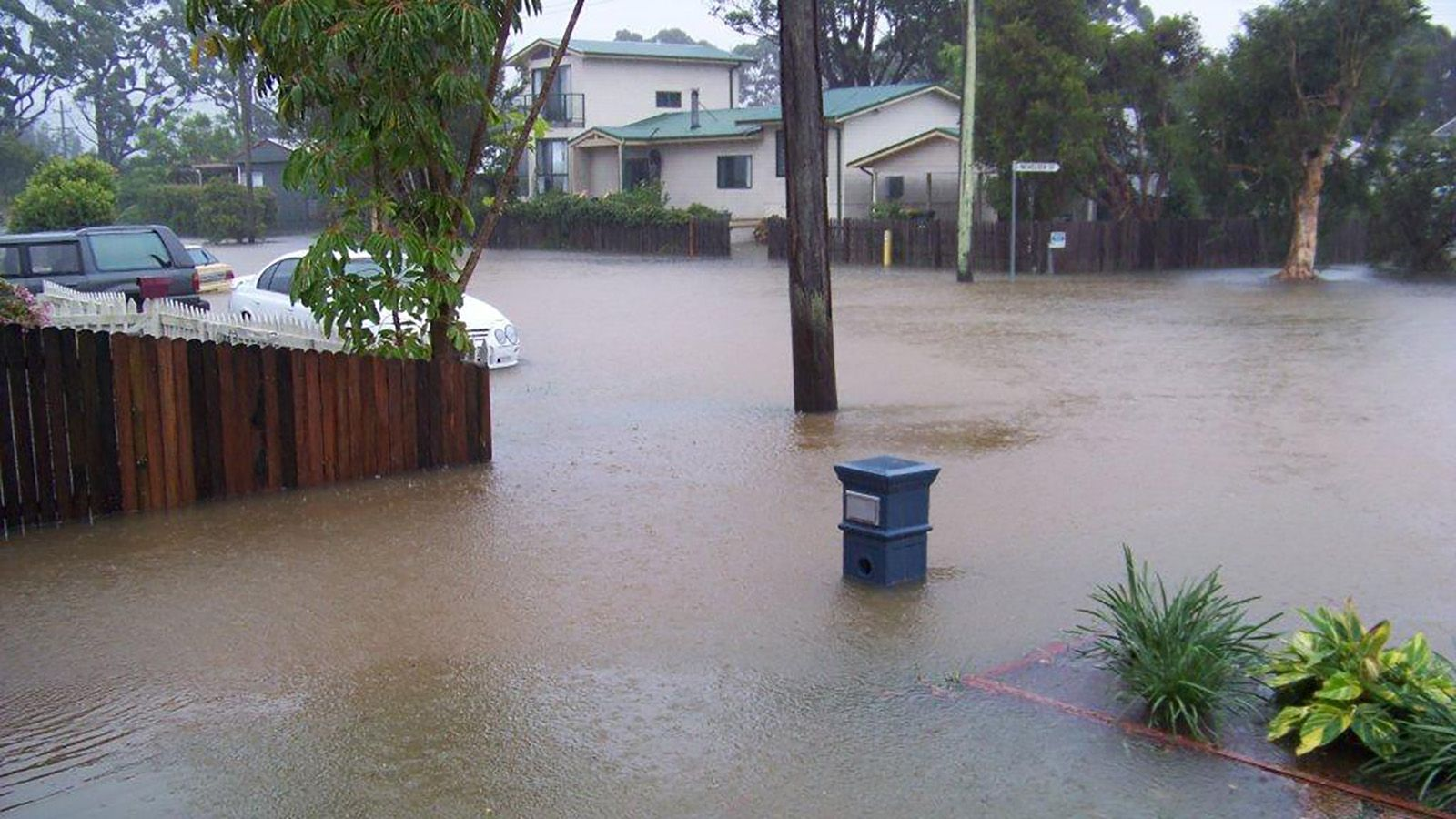 A residential street flooded with storm water banner image