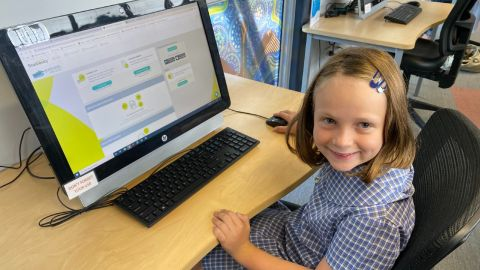 Girl in school uniform sitting at a computer.