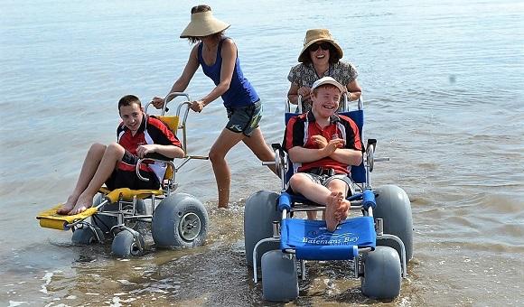 Enjoying the water wheelchairs at Corrigans Beach