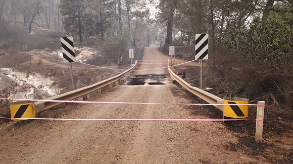 The bridge is completely burnt leaving a gapping hole in the road.